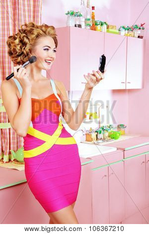 Pretty woman doing makeup on her glamorous pink kitchen at home. Beauty, fashion.