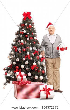 Full length portrait of a senior gentleman standing next to a Christmas tree and holding a present isolated on white background