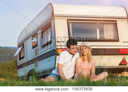 Young couple in front of a camper van