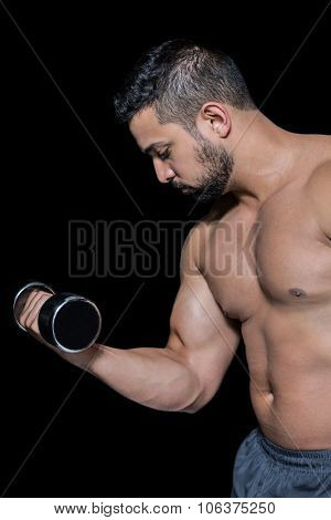 Muscular man lifting a dumbbell against blackbackground