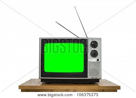 Vintage television on wood table isolated on white with chroma key green screen.