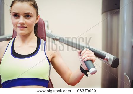 Fit woman using weights machine for arms at the gym