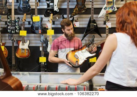 music, sale, people, musical instruments and entertainment concept - assistant showing electric guitar to customer at music store