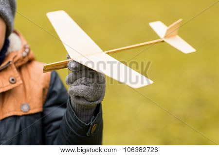 autumn, childhood, dream, leisure and people concept - close up of little boy hand holding toy plane outdoors