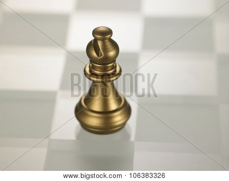 golden color chess piece bishop on glass chess board