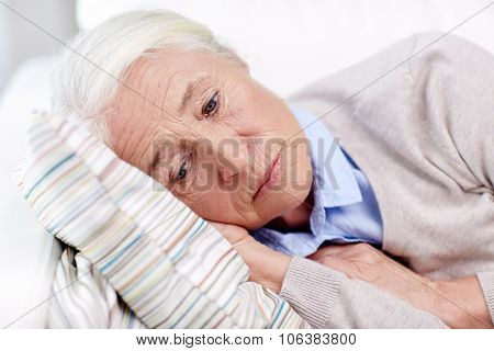age, sadness, trouble, problem and people concept - sad senior woman sleeping on pillow at home