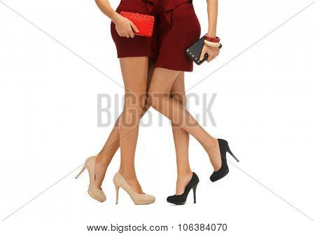 people, sale and consumerism concept - close up of two women in red dresses and high heel shoes with clutches