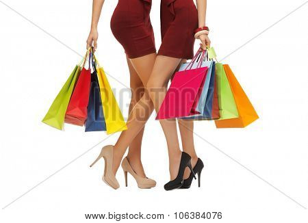 people, sale and discount concept - close up of women in red short skirts and high heeled shoes with shopping bags