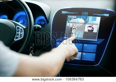 transport, modern technology, mass media and people concept - male hand pointing finger to monitor on car panel and reading news