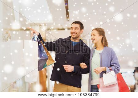 sale, consumerism and people concept - happy young couple with shopping bags pointing finger to shop window in mall with snow effect