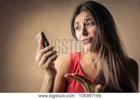 Disappointed woman looking at her smart phone