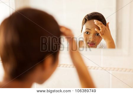 african girl checking her face for pimple looking in the mirror