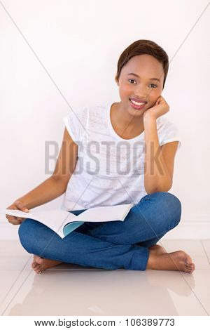 smart african american college student reading a book at home