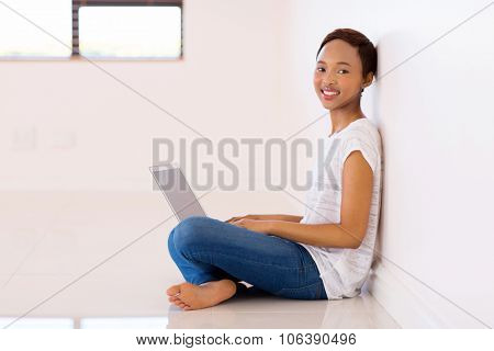 smiling afro american woman using laptop in new house