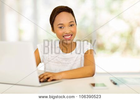 pretty afro american student using laptop