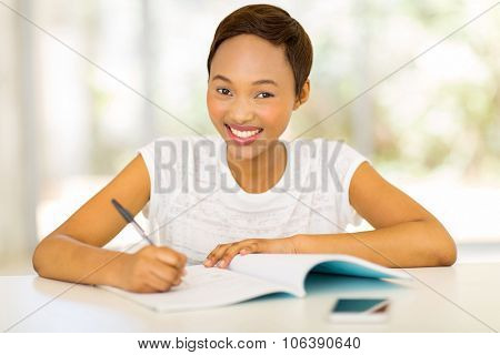portrait of pretty black college girl studying at home