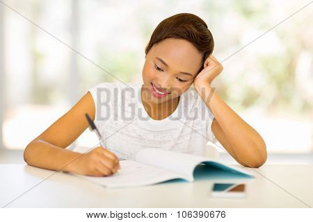 beautiful african college student writing homework at home