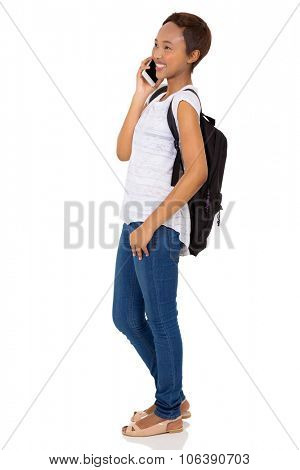 side view of happy young african american college student making a phone call