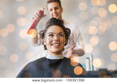 beauty, hairstyle and people concept - happy young woman with hairdresser with hair spray fixating hairdo at salon over holidays lights