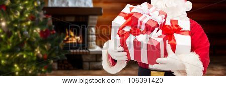 christmas, holidays and people concept - close up of santa claus with gift boxes over living room with fireplace and christmas tree background