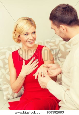 love, couple, relationship and dating concept - romantic man proposing to a woman in red dress