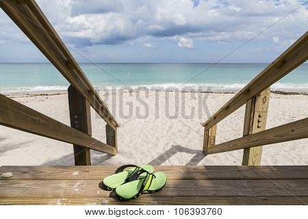 Sandals on wooden steps to the sea