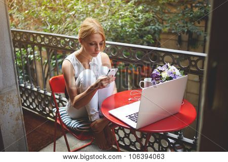 Charming female using cell telephone while sitting with net-book on a home terrace