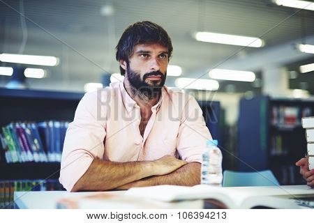 Young bearded male concentrated prepares for summaries or exams in college