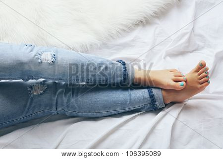 Woman in blue jeans on bed top view point
