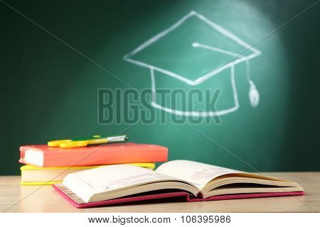 Books with scissors and bachelor hat drawing on blackboard background