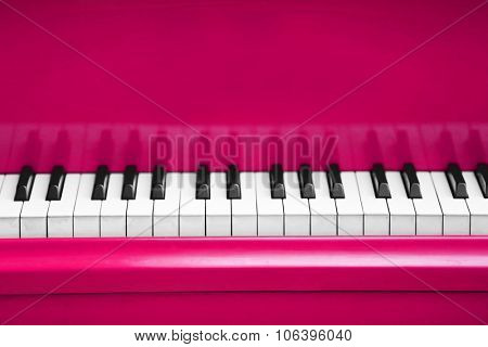 Piano keys of pink piano close up