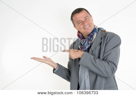 Handsome  Man  Looking At Camera And Pointing Away While Standing Against White Background