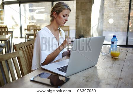 Female freelancer sitting at the wooden table with her net-book and digital tablet