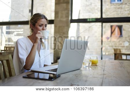 Portrait of a young beautiful businesswomen enjoying coffee during work on portable laptop computer
