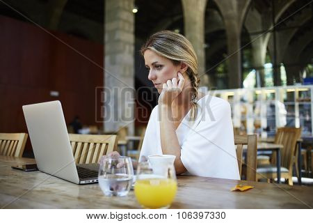 Portrait of a young attractive Sweden women connected to internet via a portable laptop computer