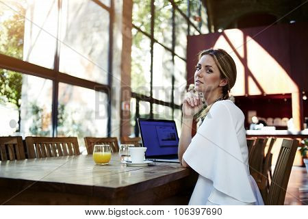 Pretty Sweden female relaxing after working on net-book during coffee break