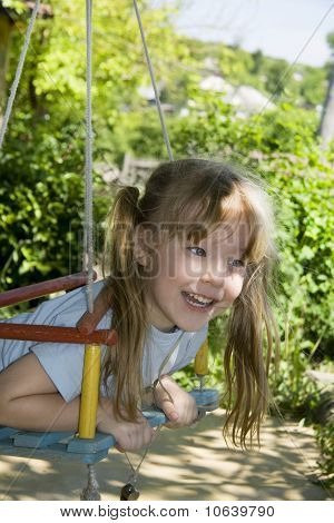 Cheerful Girl On A Swing
