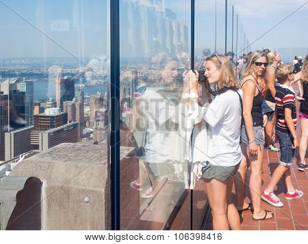 NEW YORK,USA - AUGUST 15,2015 : Tourist taking photographs from an observation deck atop a skyscraper in New York City