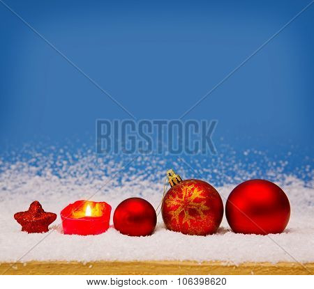 Red Christmas balls and Advent candle .