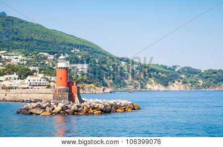 Red Lighthouse Tower On Stone Breakwater, Italy