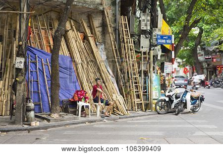 Vietnamese man selling bamboo products on an old street