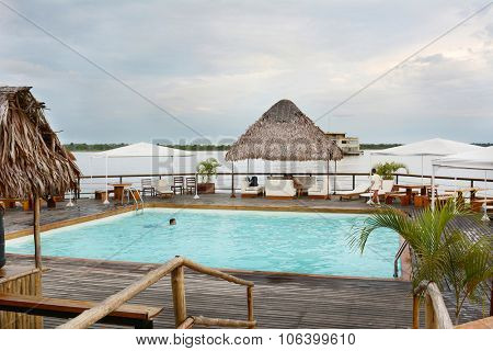 IQUITOS, PERU - OCTOBER 11, 2015: Pool at Al Frio y Al Fuego Floating Restaurant. The floating restaurant in the Itaya River features fine dining, a bar area and pool.
