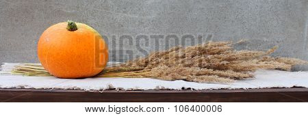 A pumpkin and a bunch of dried grass.