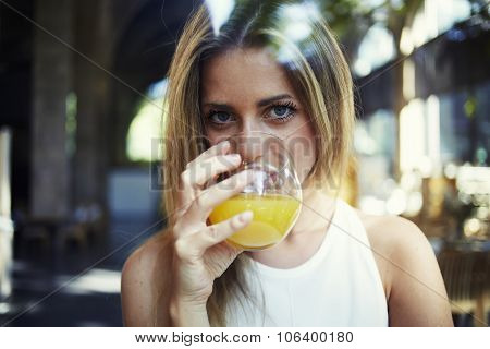 Attractive female drinking natural vitamin beverage and looking at you