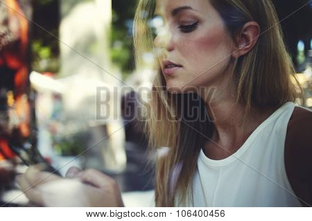 Charming blonde woman read message on cell telephone during rest after walking outdoors