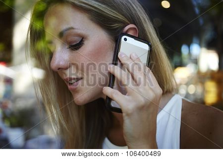 Gorgeous female having smart phone conversation with her good friend