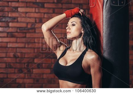 Young beautiful sexy boxer woman with red boxing bandage on hands. punching bag.  the background wal