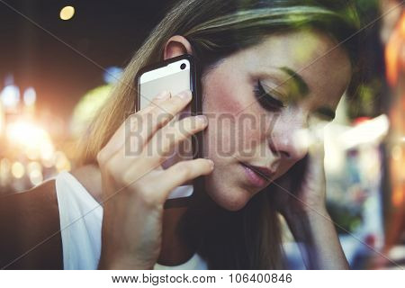 Portrait of young gorgeous woman having mobile phone conversation while sitting in coffee shop