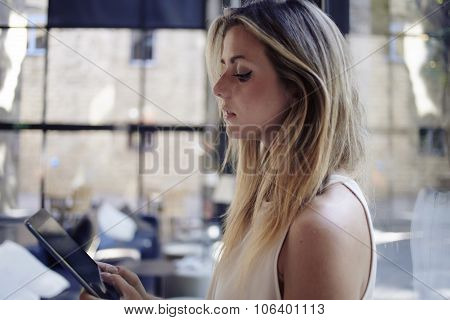 Portrait of young female student reading electronic book on digital tablet before start her lectures