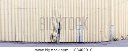 Damaged fence, behind which hides the unfinished object